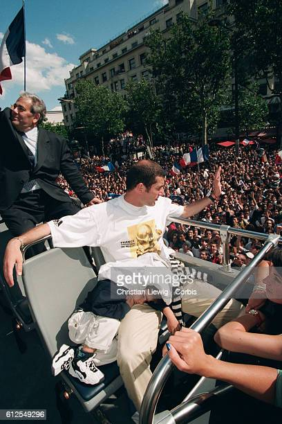 Zinedine Zidane of France's 1998 FIFA World Cup squad with his son Enzo during a parade on the Champs Elysees celebrating the team's 30 victory over...