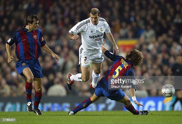 Zinedine Zidane of Real Madrid is challenged by Puyol and Philip Cocu of Barcelona during the Spanish Primera Liga match between Barcelona and Real...