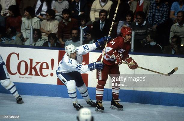 Zinetula Bilyaletdinov of the USSR is checked by Andre Dupont of the Quebec Nordiques during the 198283 Super Series on December 30 1982 at the...