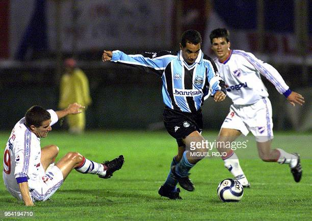 Zinho player from Gremio takes the ball in front of the mark for the players from Nacional Andres Scotti and Richard Pellejero during the game for...