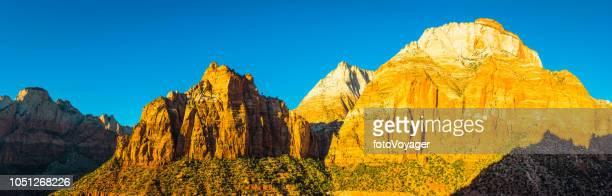 zion canyon nationalpark panorama golden dawn licht leuchtenden gipfel - erodiert stock-fotos und bilder
