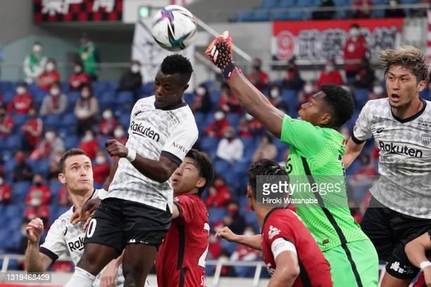 Zion Suzuki of Urawa Red Diamonds and Ayub Masika Vissel Kobe compete for the ball during the J.League Meiji Yasuda J1 match between Urawa Red...