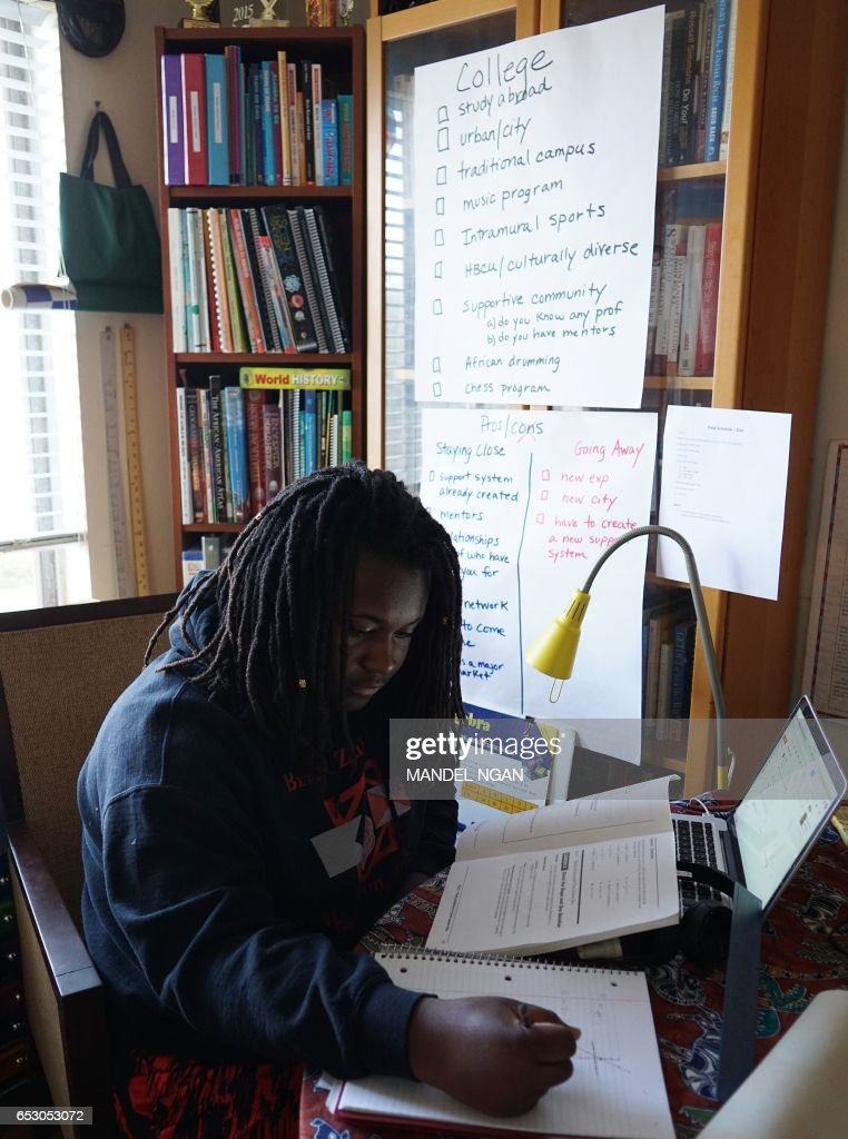 Zion, 17, who is homeschooled by his mother Monica Utsey, works at his desk at home in Washington, DC on February 24, 2017. / AFP PHOTO / MANDEL NGAN / With AFP Story by Margaret