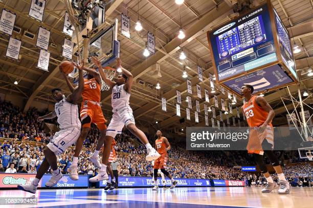 Zion Williamson and Marques Bolden of the Duke Blue Devils battle Paschal Chukwu of the Syracuse Orange for a rebound during their game at Cameron...