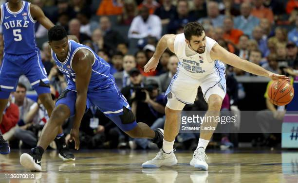 Zion Williamson of the Duke Blue Devils and Luke Maye of the North Carolina Tar Heels compete for possession during their game in the semifinals of...