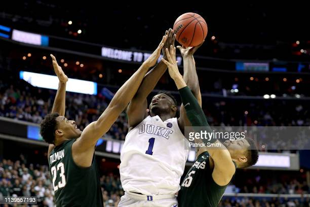 Zion Williamson of the Duke Blue Devils attempts a shot against Xavier Tillman and Kenny Goins of the Michigan State Spartans during the second half...