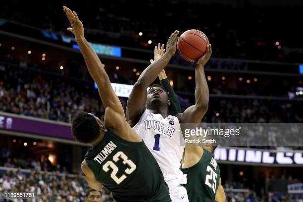 Zion Williamson of the Duke Blue Devils attempts a shot against Xavier Tillman of the Michigan State Spartans during the second half in the East...