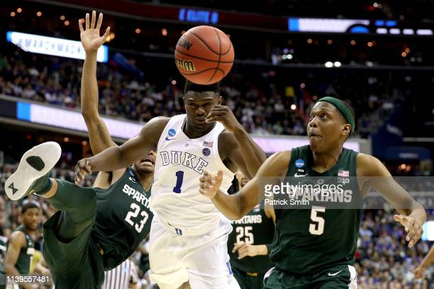 Zion Williamson of the Duke Blue Devils battles for the ball with Xavier Tillman and Cassius Winston of the Michigan State Spartans during the second...