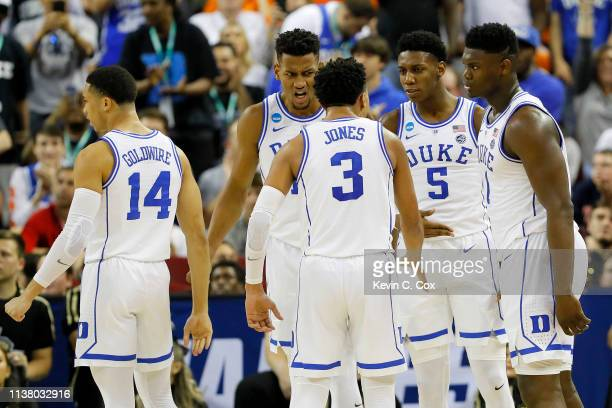 Zion Williamson of the Duke Blue Devils celebrates with RJ Barrett and Tre Jones against the UCF Knights during the first half in the second round...
