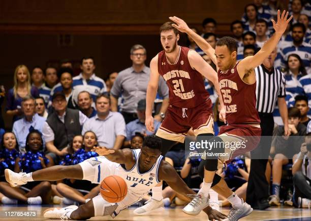 Zion Williamson of the Duke Blue Devils dives to the floor as he loses the ball under pressure from Nik Popovic and Jordan Chatman of the Boston...