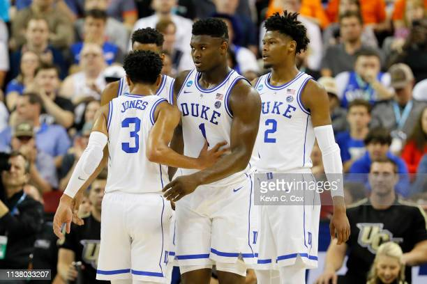 Zion Williamson of the Duke Blue Devils reacts with Tre Jones after a basket against the UCF Knights during the first half in the second round game...