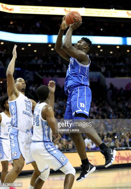 Zion Williamson of the Duke Blue Devils shoots over Kenny Williams and Garrison Brooks of the North Carolina Tar Heels during their game in the...