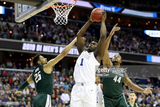 Zion Williamson of the Duke Blue Devils shoots the ball against Kenny Goins and Nick Ward of the Michigan State Spartans during the first half in the...