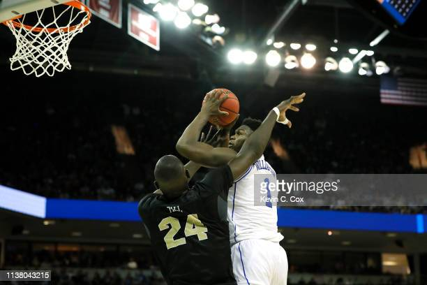 Zion Williamson of the Duke Blue Devils shoots the ball as he gets fouled by Tacko Fall of the UCF Knights during the second half in the second round...