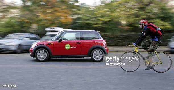 Zipcar drives past a cyclist on December 6 2006 in London England With 80000 consumer and business drivers around the world Zipcar is the worlds...