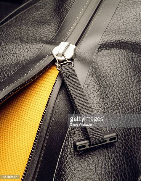 A zipper opening a black leather bag