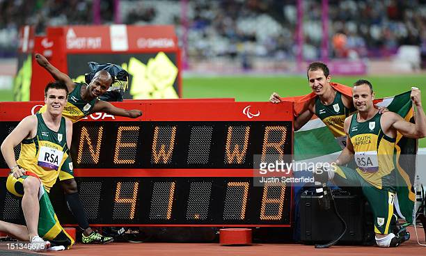 Zivan Smith Samkelo Radebe Arnu Fourie and Oscar Pistorius of South Africa pose with the timer showing their new world record after victory in the...