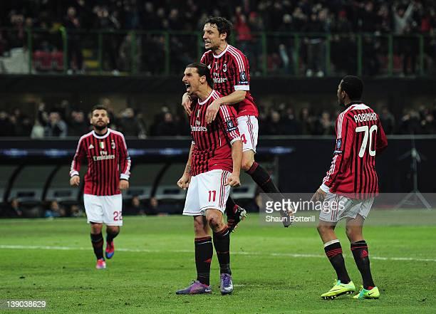 Zlatan Ibrahimovic of AC Milan celebrates scoring his penalty with Mark van Bommel during the UEFA Champions League round of 16 first leg match...