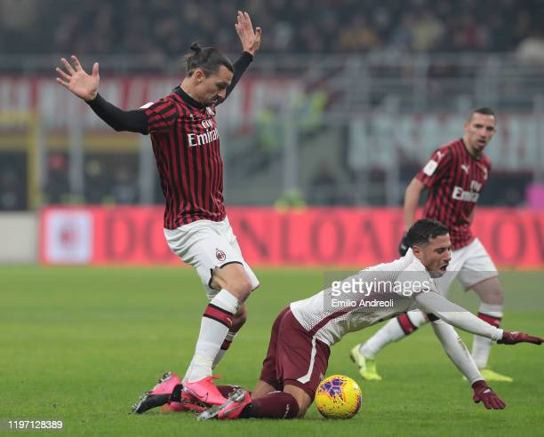 Zlatan Ibrahimovic of AC Milan competes for the ball with Armando Izzo of Torino FC during the Coppa Italia Quarter Final match between AC Milan and...