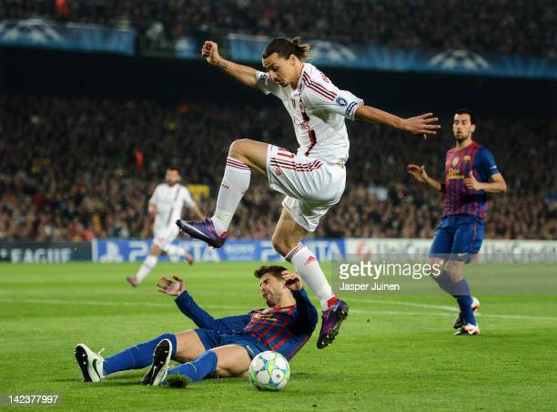 Zlatan Ibrahimovic of AC Milan duels for the ball with Gerard Pique of FC Barcelona during the Champions League quarterfinal second leg match between...