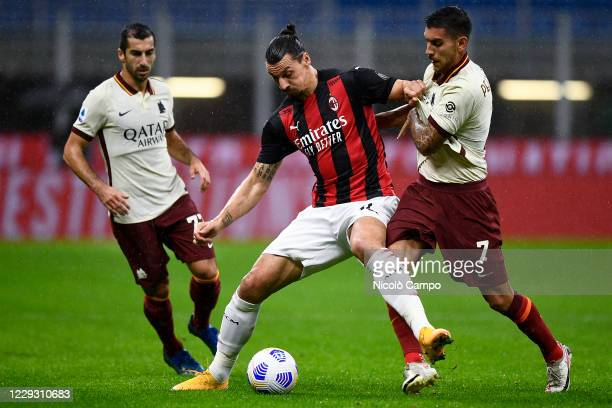 Zlatan Ibrahimovic of AC Milan is challenged by Lorenzo Pellegrini and Henrikh Mkhitaryan of AS Roma during the Serie A football match between AC...
