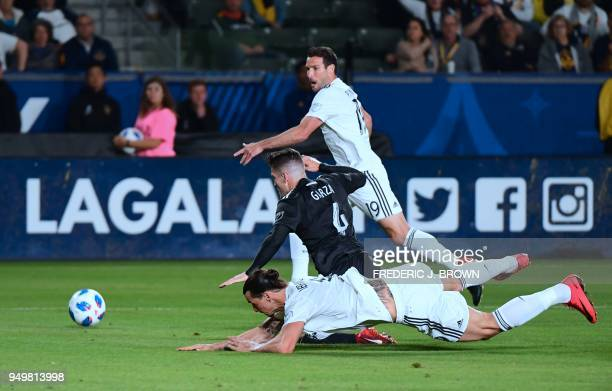 Zlatan Ibrahimovic of LA Galaxy collides with Greg Garza of Atlanta United as Chris Pontius watches in the penalty box to no avail as during their...