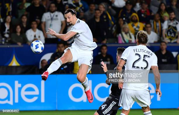 Zlatan Ibrahimovic of LA Galaxy crosses the ball under pressure from Greg Garza of Atlanta United during their Major League Soccer match in Carson...
