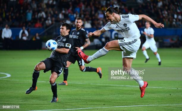 Zlatan Ibrahimovic of LA Galaxy crosses the ball under pressure from Michael Parkhurts of Atlanta United during their Major League Soccer match in...