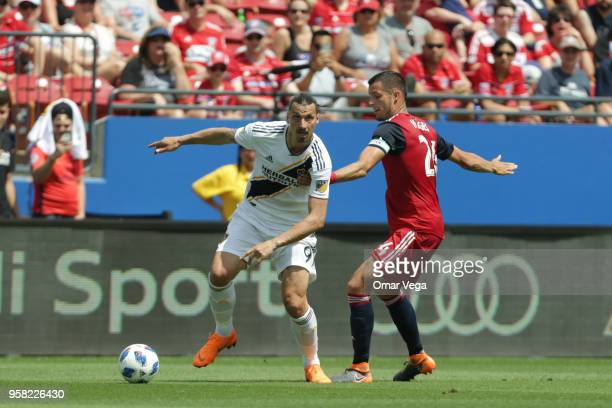 Zlatan Ibrahimovic of LA Galaxy fights for the ball with Matt Hedges of FC Dallas during the Major Soccer League match between Dallas FC and LA...