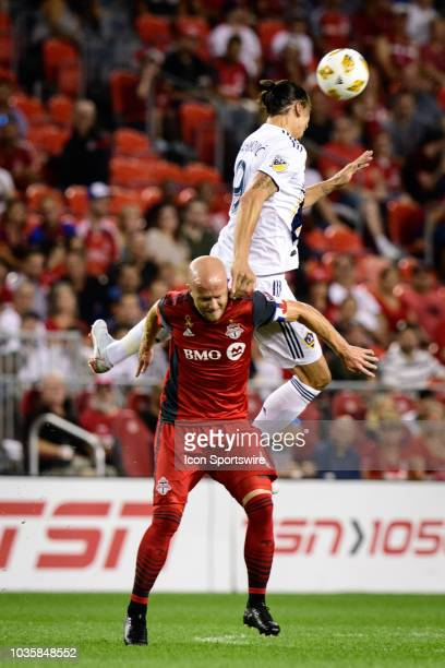 Zlatan Ibrahimovic of LA Galaxy jumps for a header over Michael Bradley of Toronto FC during the MLS regular season match between Toronto FC and LA...