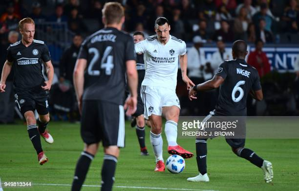 Zlatan Ibrahimovic of LA Galaxy passes under pressure from Darlington Nagbe of Atlanta United during their Major League Soccer match in Carson...
