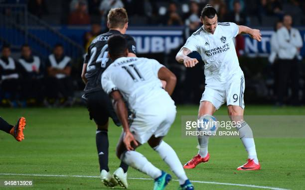 Zlatan Ibrahimovic of LA Galaxy passes under pressure from Julian Gressel of Atlanta United during their Major League Soccer match in Carson...