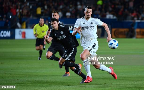 Zlatan Ibrahimovic of LA Galaxy vies for the ball with Michael Parkhurst of Atlanta United during their Major League Soccer match in Carson...