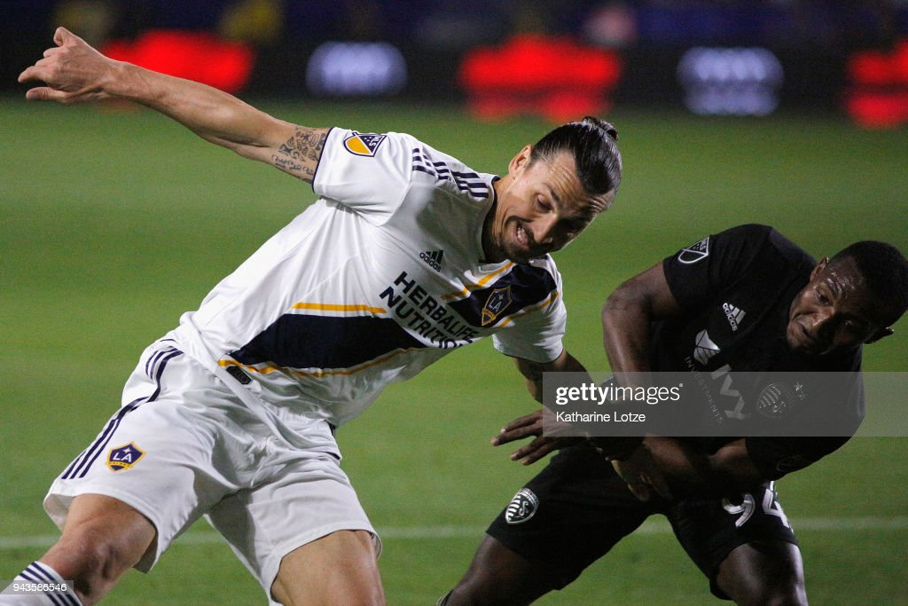 Zlatan Ibrahimovic #9 of Los Angeles Galaxy and Ike Opara #3 of Sporting Kansas City fight for control during a game against Sporting Kansas City at StubHub Center on April 8, 2018 in Carson, California.