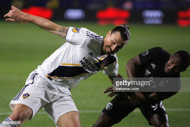 Zlatan Ibrahimovic of Los Angeles Galaxy and Ike Opara of Sporting Kansas City fight for control during a game against Sporting Kansas City at...