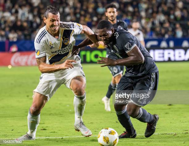 Zlatan Ibrahimovic of Los Angeles Galaxy battles Doneil Henry of Vancouver Whitecaps during the Los Angeles Galaxy's MLS match against Vancouver...