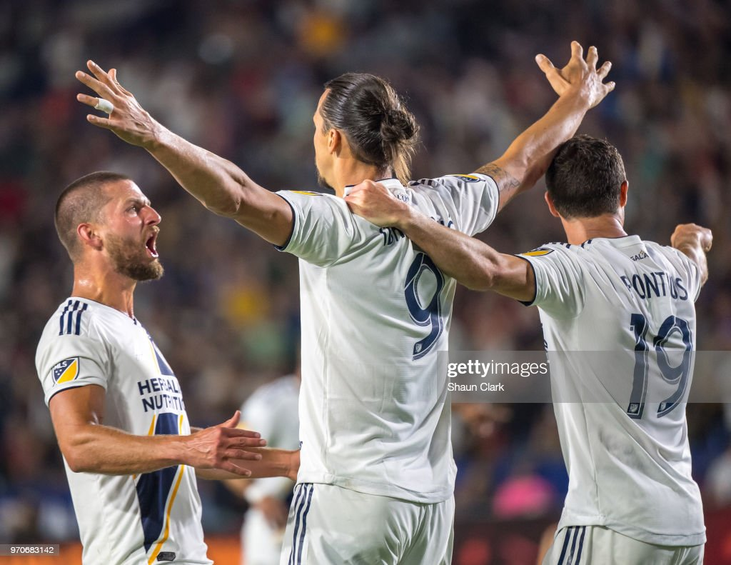 Zlatan Ibrahimovic #9 of Los Angeles Galaxy celebrates his second goal of the game as Justen Glad #15 of Real Salt Lake tries to defend during the Los Angeles Galaxy's MLS match against FC Dallas at the StubHub Center on June 9, 2018 in Carson, California. Los Angeles Galaxy won the match 3-0