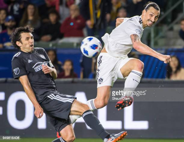 Zlatan Ibrahimovic of Los Angeles Galaxy crosses the ball as Michael Parkhurst of Atlanta United defends during the Los Angeles Galaxy's MLS match...