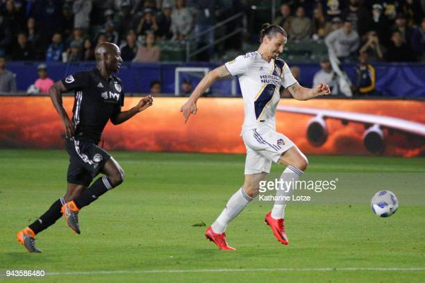 Zlatan Ibrahimovic of Los Angeles Galaxy dribbles past Ike Opara of Sporting Kansas City toward the goal during a game against Sporting Kansas City...
