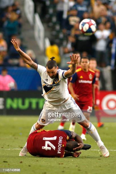 Zlatan Ibrahimovic of Los Angeles Galaxy falls over Nedum Onuoha of Real Salt Lake during the second half of a game at Dignity Health Sports Park on...