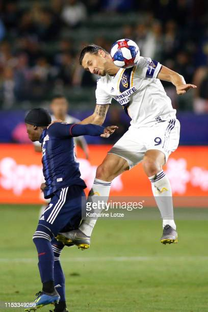 Zlatan Ibrahimovic of Los Angeles Galaxy reacts to a header as he pushes off the shoulder of Luis Caicedo of New England Revolution during the second...