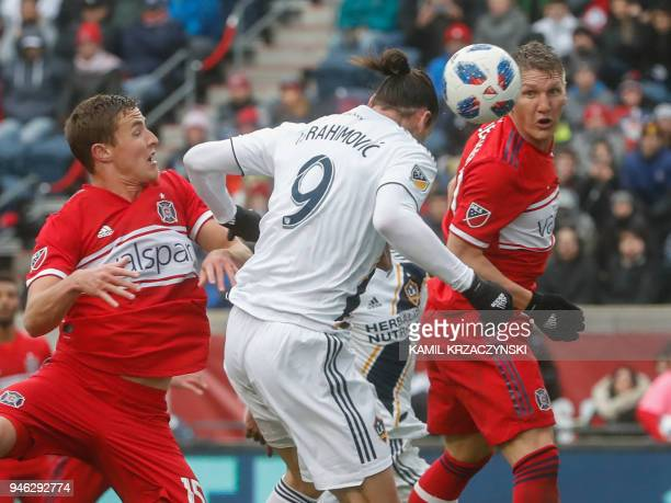Zlatan Ibrahimovic of Los Angeles Galaxy scores with a header against Grant Lillard and Bastian Schweinsteiger of Chicago Fire during the first half...