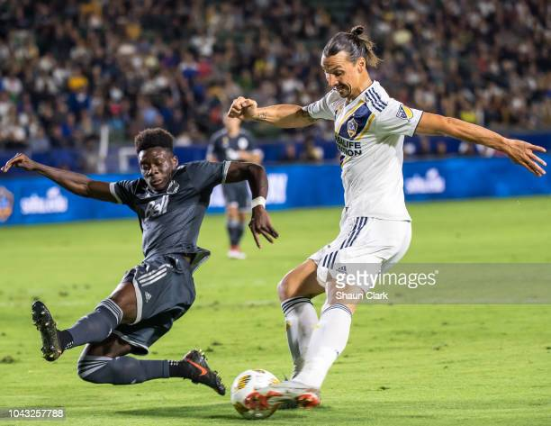 Zlatan Ibrahimovic of Los Angeles Galaxy takes a shot as Marcel de Jong of Vancouver Whitecaps defends during the Los Angeles Galaxy's MLS match...