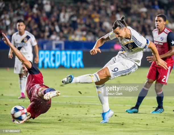Zlatan Ibrahimovic of Los Angeles Galaxy takes a shot as Matt Hedges of FC Dallas flies in to block the shot during the Los Angeles Galaxy's MLS...