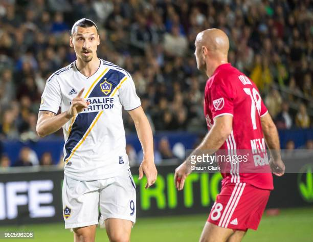 Zlatan Ibrahimovic of Los Angeles Galaxy talks to Aurelien Collin of New York Red Bulls durig the Los Angeles Galaxy's MLS match against New York Red...