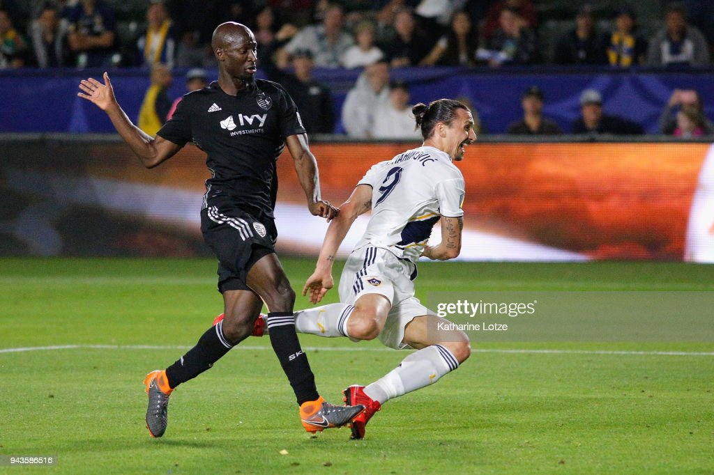 Zlatan Ibrahimovic #9 of Los Angeles Galaxy trips on Ike Opara #3 of Sporting Kansas City during a game at StubHub Center on April 8, 2018 in Carson, California.