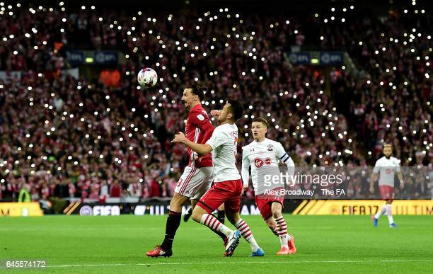 Zlatan Ibrahimovic of Manchester United holds off Maya Yoshida of Southampton as Southampton fans light up the stadium during the EFL Cup Final...