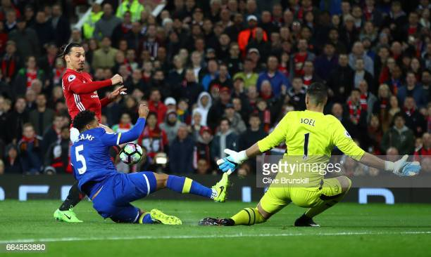 Zlatan Ibrahimovic of Manchester United shoots as Ashley Williams of Everton attempts to block and Joel Robles of Everton attempts to save during the...
