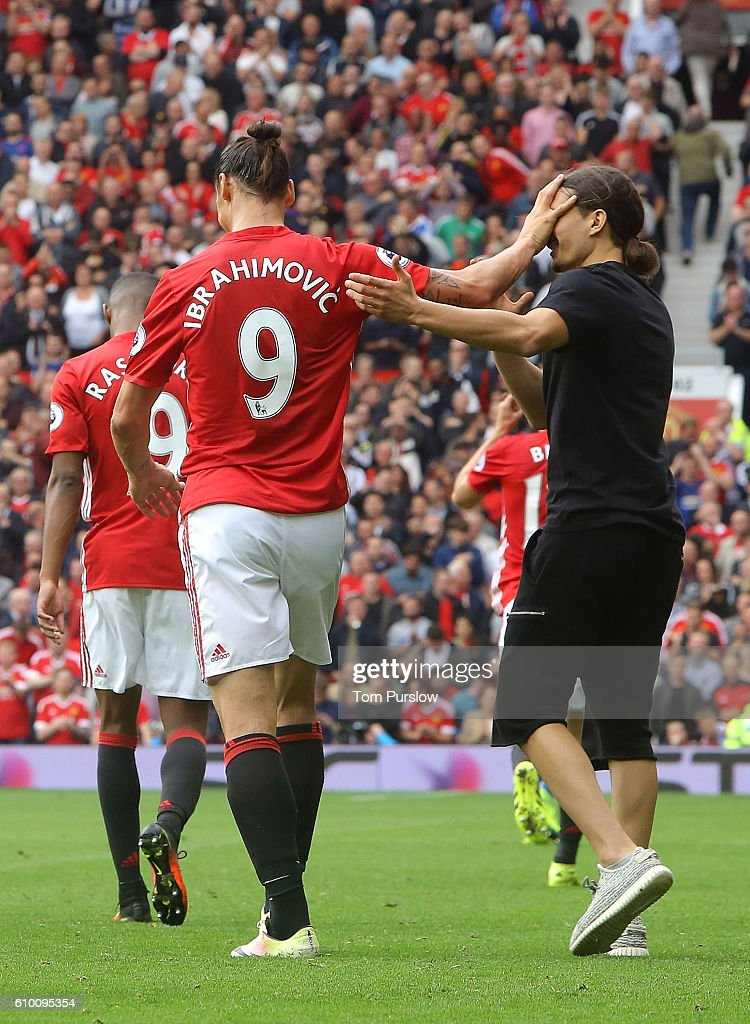 Zlatan Ibrahimovic of Manchester United shrugs off a pitch invader during the Premier League match between Manchester United and Leicester City at Old Trafford on September 24, 2016 in Manchester, England.