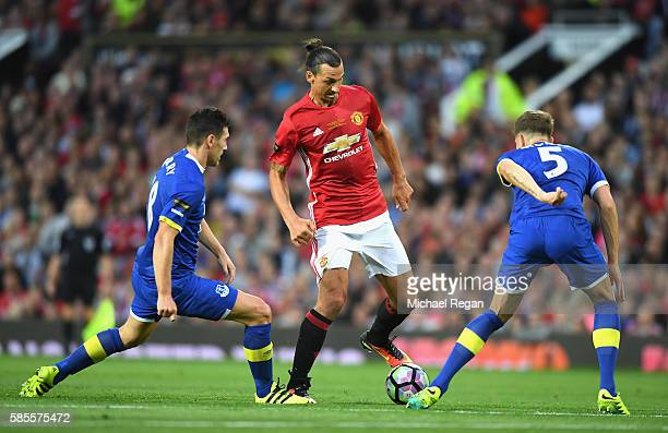 Zlatan Ibrahimovic of Manchester United takes on John Stones and Gareth Barry of Everton during the Wayne Rooney Testimonial match between Manchester...